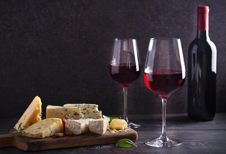 Red wine with cheese on chopping board. Wine and food concept - Image Stock Photo