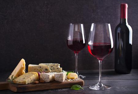 Vino tinto con queso sobre una tabla de cortar. Concepto de vino y comida - Imagen Foto de archivo