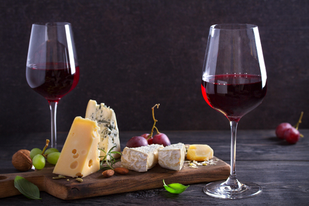 Red wine with cheese on chopping board. Wine and food concept - Image Imagens