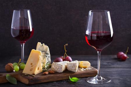 Vino tinto con queso sobre una tabla de cortar. Concepto de vino y comida - Imagen