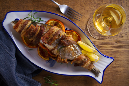 Grilled bacon-wrapped fish with oranges and rosemary, served with lemons - Image