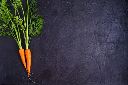 Carrots - root vegetables on a black background. Summer farm vegetables. Food background, layout, room for text Banco de Imagens