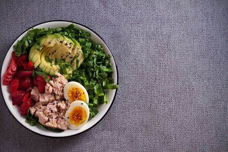 Tuna strawberry avocado egg and spinach salad in bowl - healthy food Stockfoto