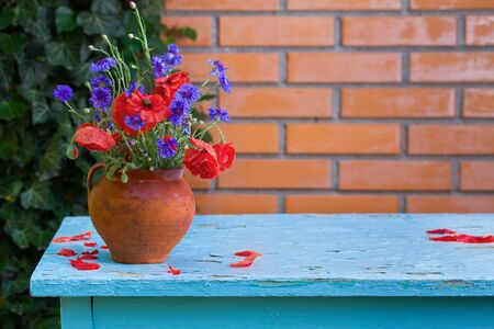 Bouquet of wildflowers - cornflowers and poppies in vase on table beside brick wall background in garden. View with copy space 写真素材