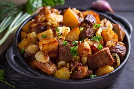 Manzo fritto e patate con cipolle e aglio serviti in un piatto nero su fondo di legno Archivio Fotografico