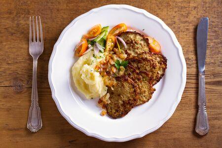 Rundleverpannekoeken met aardappelpuree en groenten. Lever bijgerecht. Uitzicht van bovenaf, top studio opname