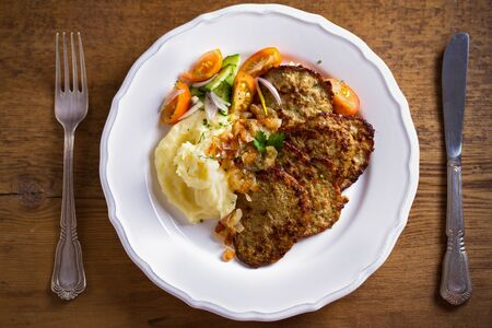 Chicken liver pancakes with mashed potato and vegetables on white plate. Liver side dish