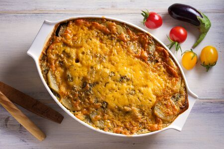 Traditional moussaka in baking dish on white wooden table. View from above, top studio shot Imagens