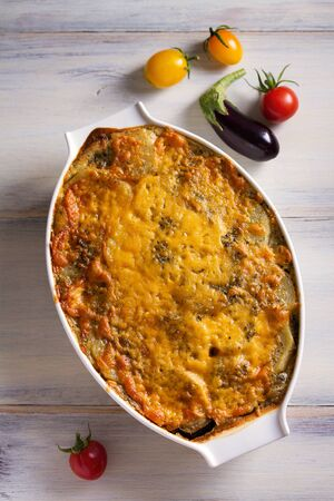 Traditional moussaka in baking dish on white wooden table. View from above, top studio shot 写真素材