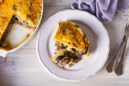 Traditional moussaka on plate and in baking dish