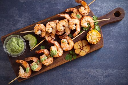 Skewered shrimps with garlic butter sauce served with cilantro and lime on serving board 版權商用圖片