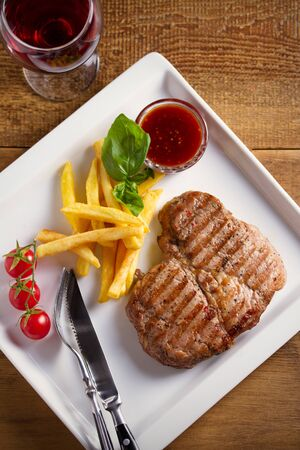 Grilled pork steak with fries, sauce and vegetables on white plate. Glass of red wine