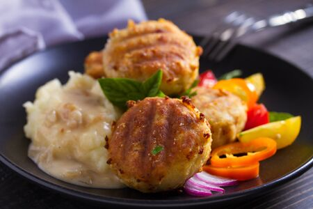 Fish cakes with mashed potatoes and vegetables. Fish patties. Fried cutlets of minced fish Фото со стока - 129769322