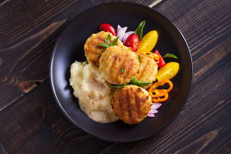 Fish cakes with mashed potatoes and vegetables. Fish patties. Fried cutlets of minced fish. View from above, top studio shot