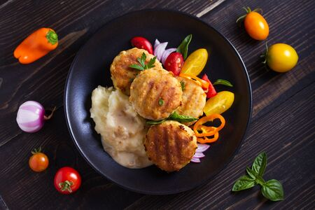 Fish cakes with mashed potatoes and vegetables. Fish patties. Fried cutlets of minced fish. View from above, top studio shot Фото со стока - 129769346