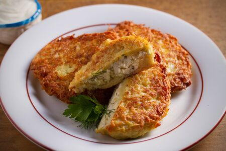 Potato Pancakes Stuffed With Cottage Cheese. Homemade vegetable fritters on white plate, wooden table Reklamní fotografie
