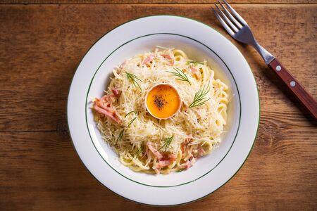 Carbonara pasta, spaghetti with pancetta, egg, parmesan cheese and cream sauce. Pasta alla carbonara - Italian cuisine dish Foto de archivo - 129769616