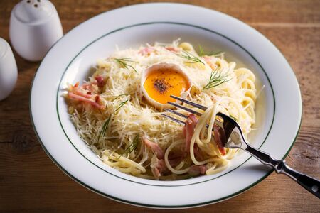 Carbonara pasta, spaghetti with pancetta, egg, parmesan cheese and cream sauce. Pasta alla carbonara - Italian cuisine dish Foto de archivo - 129769620