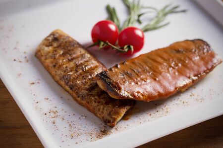 Grilled mackerel fish fillet in tomato mustard sauce, served with cherry tomatoes, rosemary and lemon on white plate, wooden table