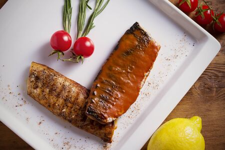Grilled mackerel fish fillet in tomato mustard sauce, served with cherry tomatoes, rosemary and lemon on white plate, wooden table Stok Fotoğraf - 129769623