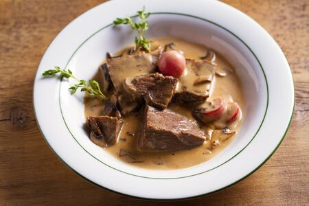 Braised veal cheeks in cream sauce with mushrooms Imagens