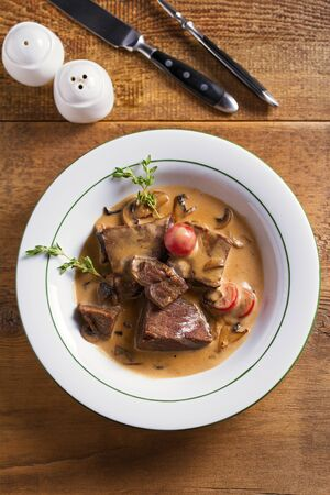 Braised veal cheeks in cream sauce with mushrooms. View from above, top studio shot Imagens