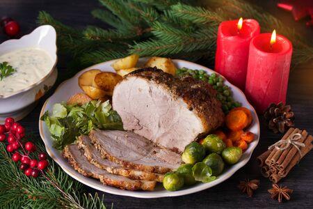 Prosciutto al forno con verdure: patate, carote, cavolini di Bruxelles, cavoli, piselli e salsa. Decorazioni natalizie. Piatto per la vigilia di Natale