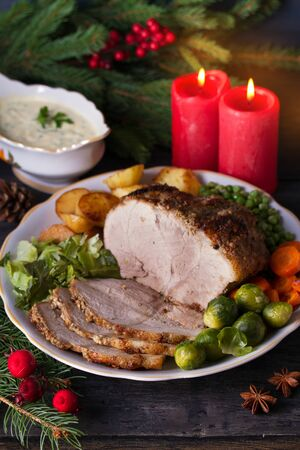 Baked ham with vegetables: potatoes, carrots, brussel sprouts, cabbage, green peas and sauce. Christmas decorations. Dish for Christmas Eve Imagens