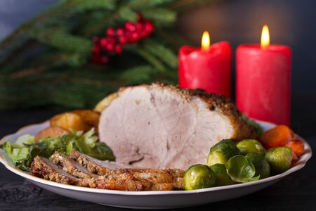Baked ham with vegetables: potatoes, carrots, brussel sprouts, cabbage and green peas. Christmas decorations. Dish for Christmas Eve Imagens