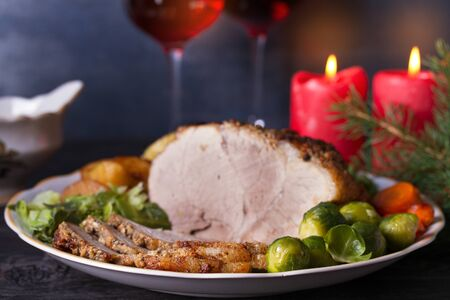Baked ham with vegetables, two glasses of red wine. Christmas decorations. Dish for Christmas Eve Imagens