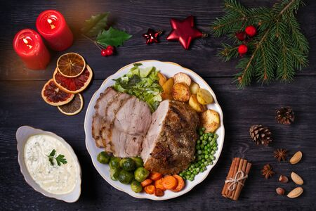 Baked ham with vegetables: potatoes, carrots, brussel sprouts, cabbage, green peas and sauce. Christmas decorations. Dish for Christmas Eve. View from above, top studio shot