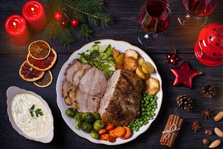 Baked ham with vegetables two glasses of red wine. Christmas decorations. Dish for Christmas Eve. View from above, top studio shot Imagens