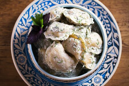 Dumplings filled with potato in sour cream, blue bowl on wooden table - overhead, horizontal
