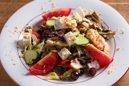 Healthy vegetarian food: tomato, cucumber, lettuce and mushroom salad with feta cheese and walnuts. Close up, horizontal
