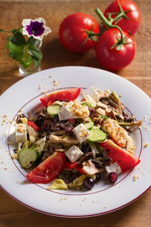Healthy vegetarian food: tomato, cucumber, lettuce and mushroom salad with feta cheese and walnuts