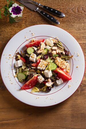 Healthy vegetarian food: tomato, cucumber, lettuce and mushroom salad with feta cheese and walnuts. View from above, top studio shot