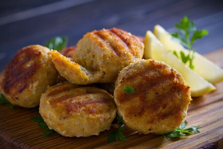 Fish cakes with lemon and herbs. Fish patties on wooden board 写真素材