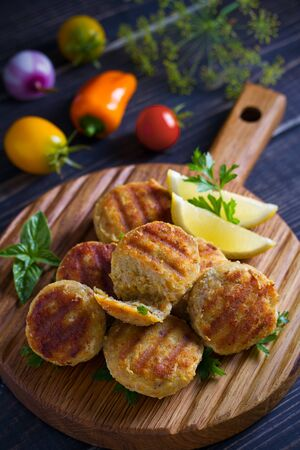 Fish cakes with lemon and herbs. Fish patties on wooden board Stock Photo