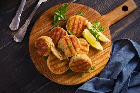 Fish cakes with lemon and herbs. Fish patties on wooden board. Overhead, horizontal image