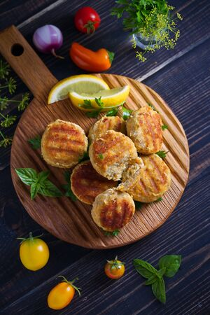 Fish cakes with lemon and herbs. Fish patties on wooden board. Overhead, vertical image 写真素材