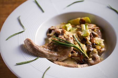 Veal tongues with stewed vegetables and cream sauce, garnished with rosemary