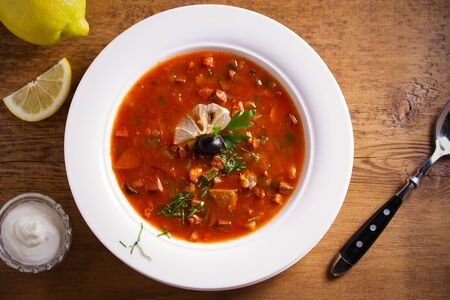 Solyanka - thick, spicy and sour Russian soup, made of beef, ham, sausages, chicken breast cucumber pickles and tomatoes