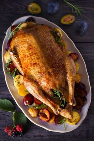 Baked duck with potatoes, plums, rosemary and thyme, close-up on plate. Overhead, vertical