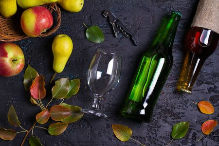 Bottles and glass of apple and pear cider with fruits on black background. View from above, top view Stock Photo