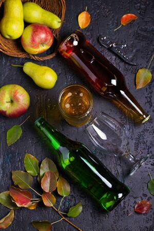 Bottles and glass of apple and pear cider with fruits on black background. Selective focus on glass with cider. View from above, top view