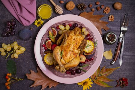 Whole roast chicken or turkey with fruits, vegetables and berries. Autumn decorations on the table. Autumn food background, flat lay