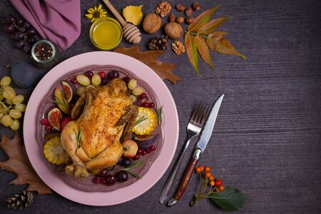 Whole roast chicken or turkey with fruits, vegetables and berries. Autumn decorations on the table. Autumn food background, flat lay. Room for text, copy space