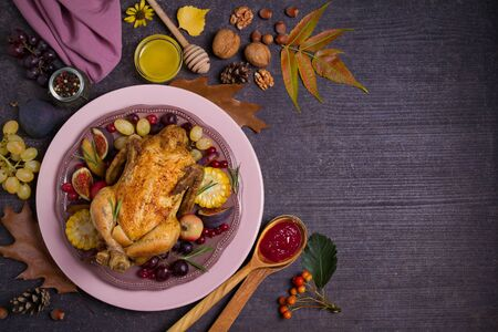 Whole roast chicken or turkey with fruits, vegetables, berries and cranberry sauce. Autumn food background, flat lay. Room for text, copy space