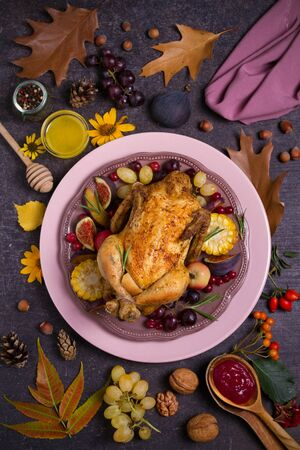Whole roast chicken or turkey with fruits, vegetables, berries and cranberry sauce. Autumn decorations on the table. Autumn food background, flat lay Banco de Imagens