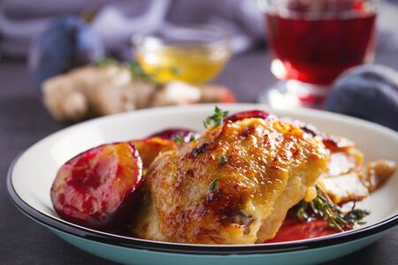 Baked chicken and plums in ginger, honey and red wine sauce with thyme. Horizontal image Stock Photo
